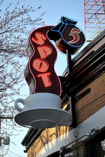 Neon sign for Spot with a coffee pot pouring coffee into a mug, in Seattle, Washington.