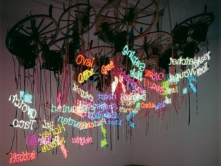 Neon words suspended from wheels to create an art display.