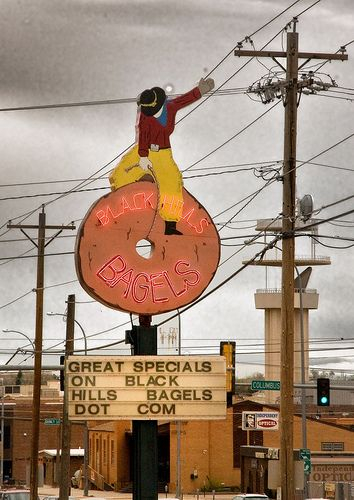 Cowboy on a bagel and neon text sign placed on the bagel, signage of Blackhills Bagels.
