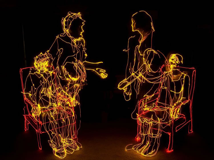 Creative installation using bright neon light people figures.
