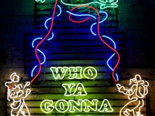 """Ghostbusters movie scene recreated with neon lights and the famous slogan """"Who ya gonna call?""""."""