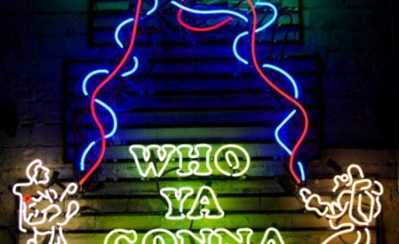 "Ghostbusters movie scene recreated with neon lights and the famous slogan ""Who ya gonna call?""."