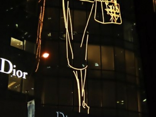 Huge neon sign representing a beautiful elegant woman for the Dior flagship store in 57th street in New York City.