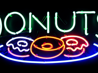 Cute donuts neon sign with text and pretty donuts on a plate.
