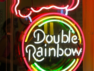 """Ice cream cone with a circle on it and the text """"Double Rainbow"""" neon sign."""