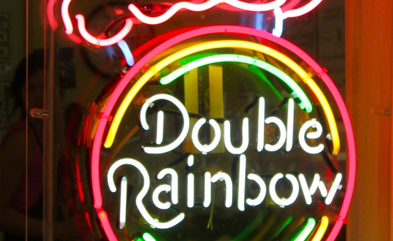 "Ice cream cone with a circle on it and the text ""Double Rainbow"" neon sign."
