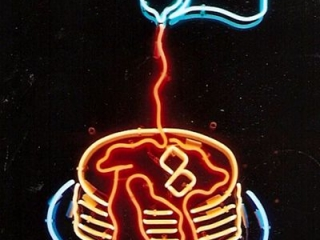 Pancakes on a plate, with melted butter and syrup pouring on them neon sign.
