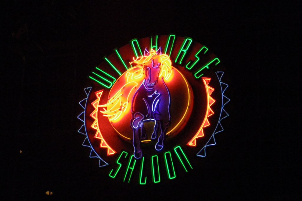 Neon sign in the shape of a horse within a circle and the name Wildhorse Saloon around it.