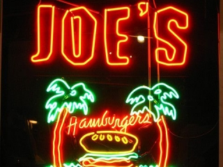 Hamburger on an island between two palm trees, neon sign for Joe's Hamburgers.