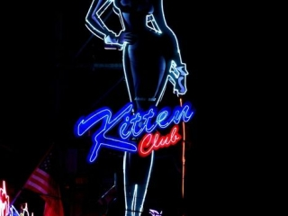 """Giant Catwoman figure with neon wire and the name """"Kitten Club"""" neon sign."""