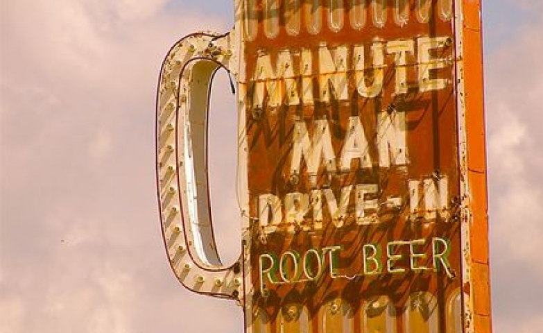 Giant glass with lettering give shape to a neon sign for Minute Man Drive-In Root Beer.