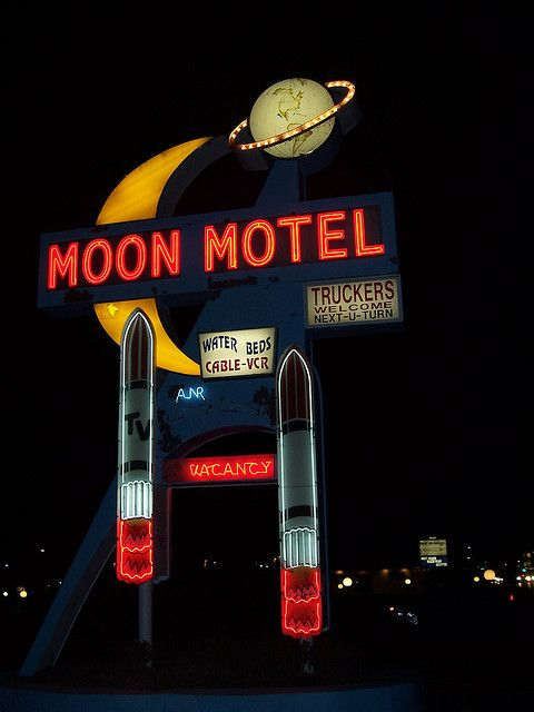 Vintage neon sign displaying elements related with the name of the Moon Motel such as rockets and two moons.