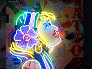 Neon sign in the shape of  girl's head and shoulders for a tattoo shop.