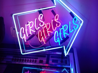 """Neon sign in the shape of an arrow with the word """"Girls"""" inside it three times."""