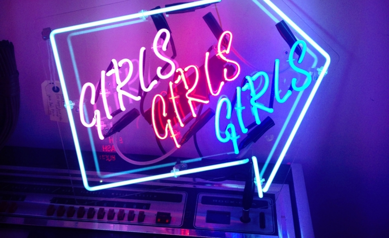 "Neon sign in the shape of an arrow with the word ""Girls"" inside it three times."
