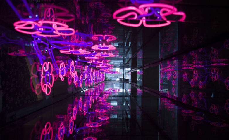 A corridor design filled with flowers made with neon light.