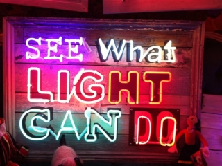 """Creative sign made with neon light and the appropriate text """"See what light can do""""."""