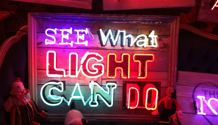 "Creative sign made with neon light and the appropriate text ""See what light can do""."