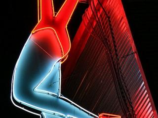 Neon sign with half scissors and half female legs.