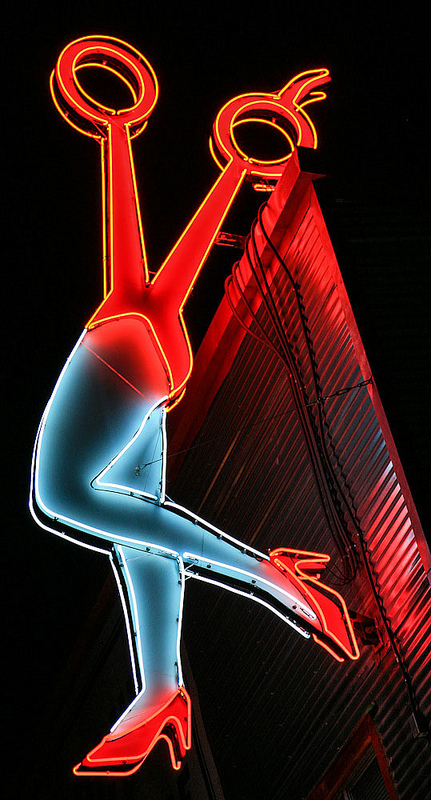 Neon sign with half scissors and half female legs.