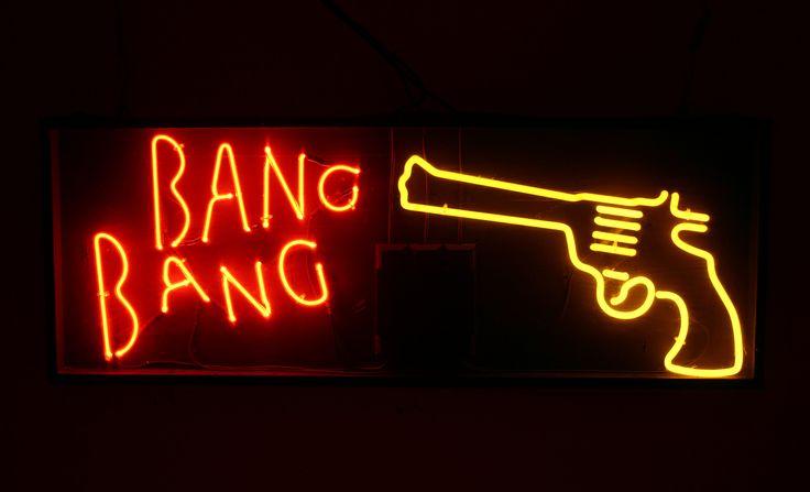 Neon lights used to make a sign of a gun that shoots the words Bang Bang.