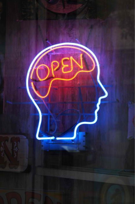A sign for creative people, neon light used to make a head shape with the word Open in the brain area.