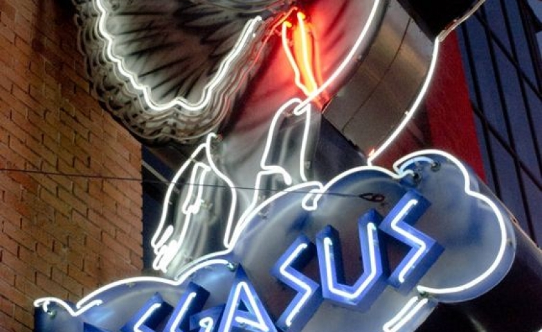 Neon sign for the Pegasus restaurant with an iconic Pegasus and a man trying to tame it.
