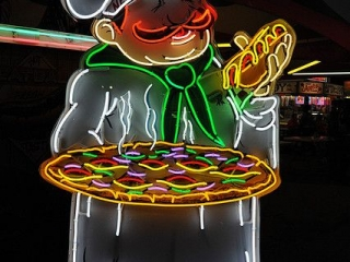 A fine neon sign for a diner or a restaurant representing a chef holding a pizza and a hot dog.