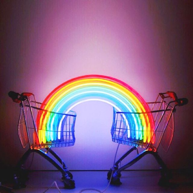 Cute and colorful rainbow neon light placed between two shopping carts.