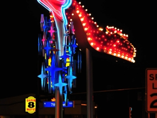 Sign made with neon light representing a showgirl, stars and a woman's red shoe.