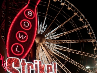 The location of the Strike! Rock N'Bowl really helps its neon sign to make a beautiful setting with a big ferris wheel in the background.