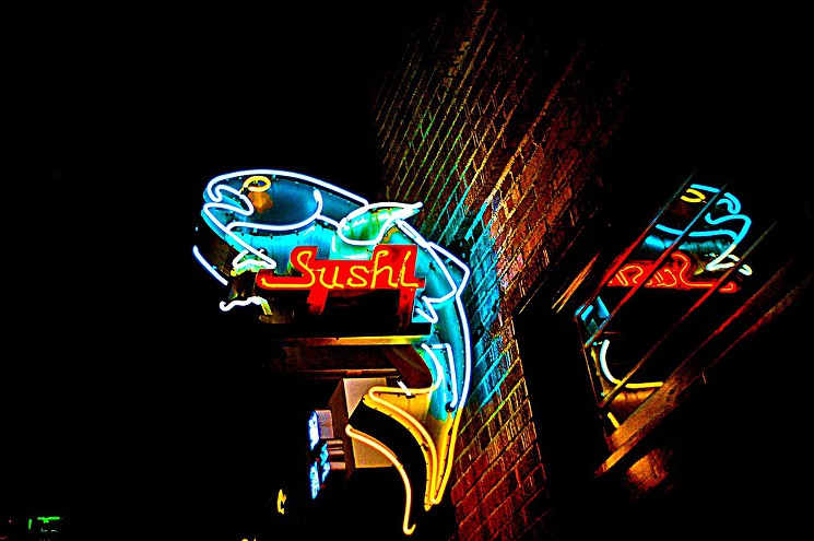 Neon sign for a sushi restaurant with the figure of a big fish made with neon lights.