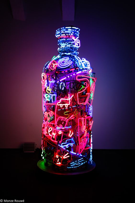Very creative and remarkable neon sign with different items made with neon wire and placed to create the shape of a bottle.