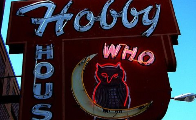 An owl sitting on the moon - retro neon sign for a shop called Who's Hobby House.