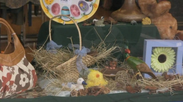 Rustic kind of Easter decoration for the window display, with a basket filled with hay, a chick, and a framed flower.