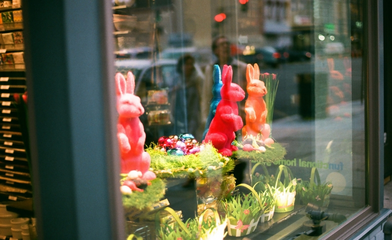 The powerful colors on the rabbits and the baskets with green grass are fitting well the Easter window display.