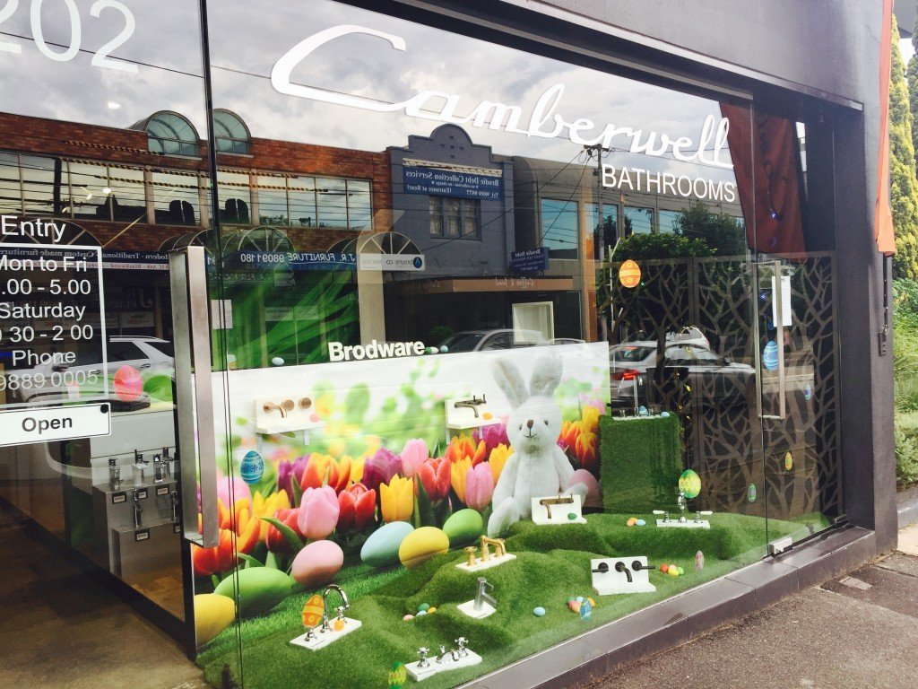 Artificial grass on the floor of the window display, the bathroom objects are placed there, and the background it is formed by a banner with a rabbit, flowers and eggs for Easter.