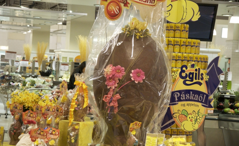 A big chocolate egg, decorated for Easter with pink flowers. This window display has also other little eggs and yellow flowers.