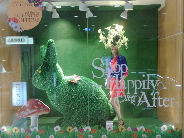 A green background, with an Easter tint with a big shape of a rabbit made from artificial grass, and a mushroom sticker.