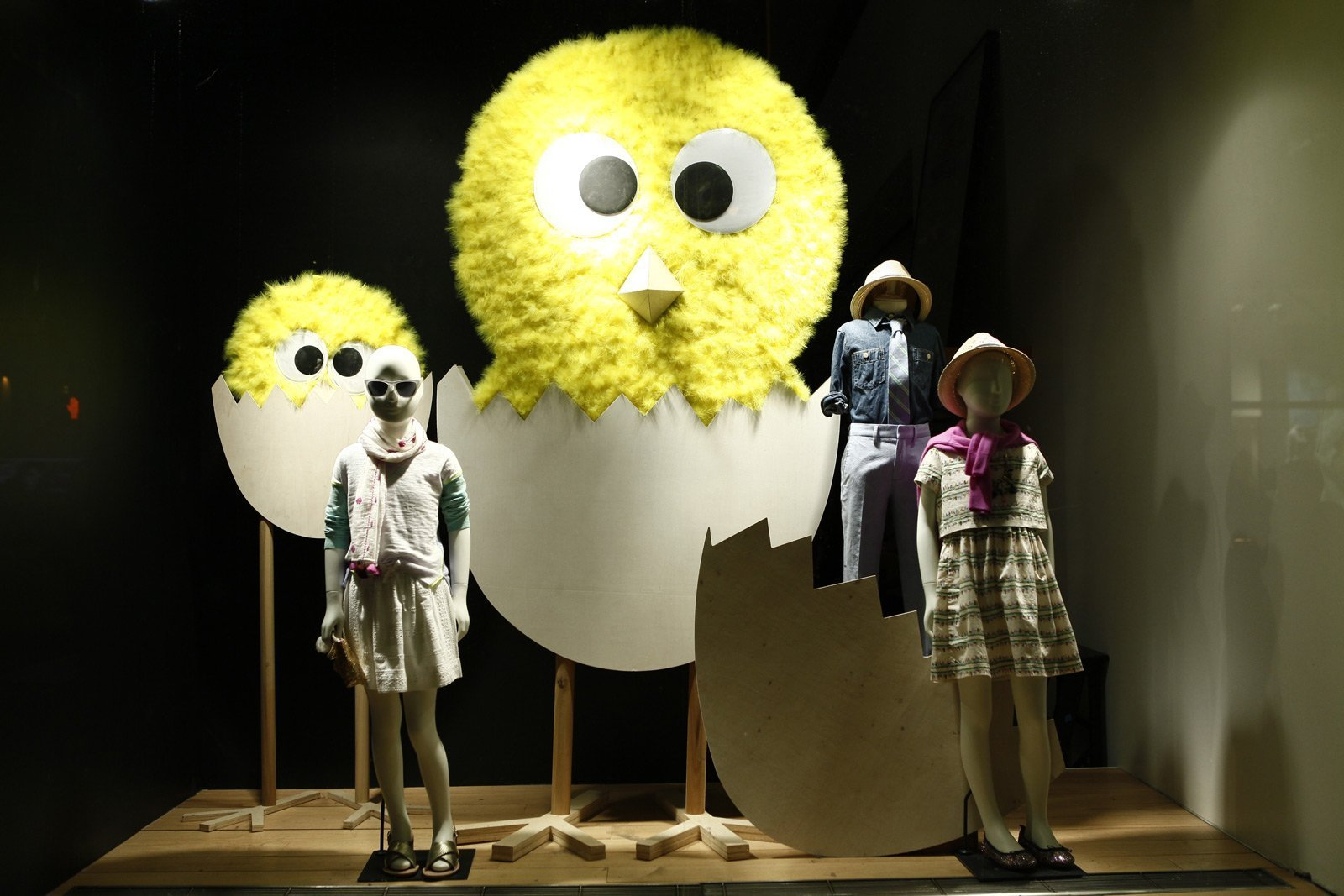 This it's a kids store window display, decorated for Easter with chicks getting out from eggs, made from a board, wood and yellow feathers.