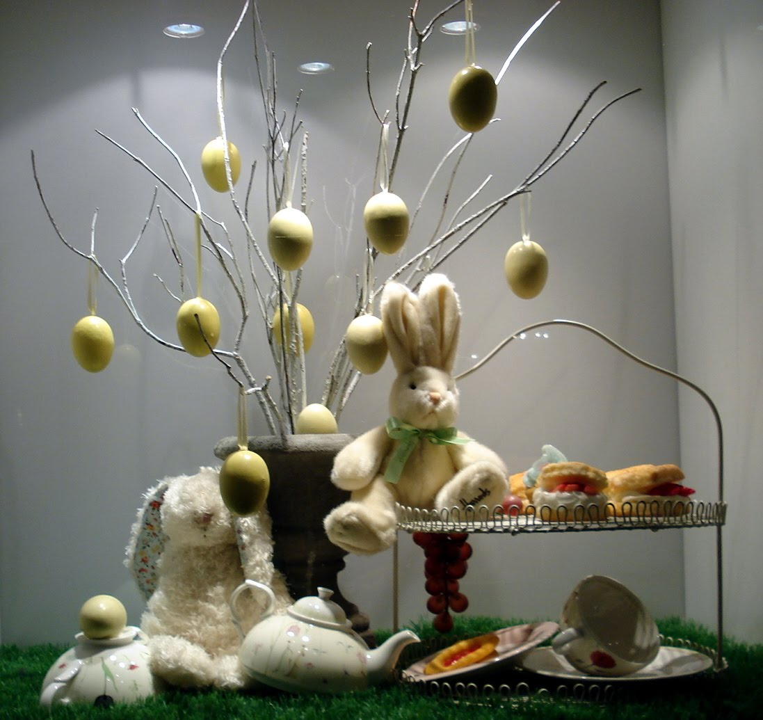In this photo of the Easter window display, we have a few branches from which are hanged eggs, and two cute plush bunnies, having tea.