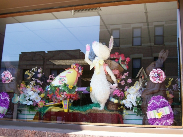 In this Easter window display we see Easter bunny, flowers and in the right part we can see another Easter bunny which seems made from chocolate.