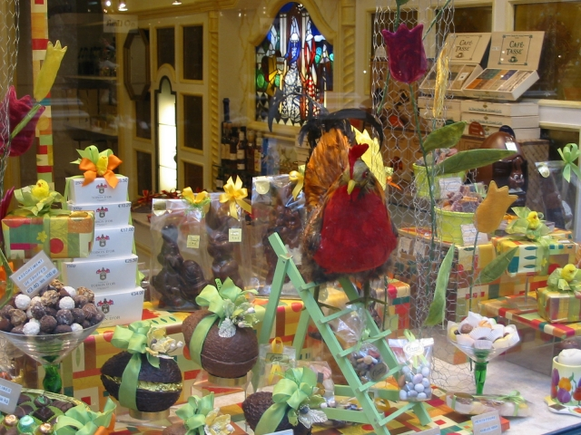 A chick on a scale with some chocolate eggs decorated with bows, that could be its work. An Easter window display based on chocolate.