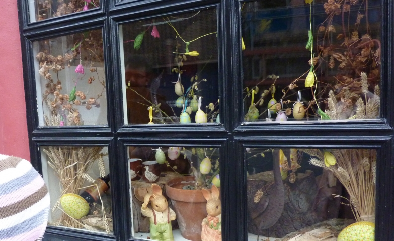 A child being excited by the decorated window display, with Easter eggs and rabbits.
