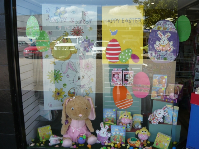 A childish Easter window display with childish banners, coloring books and plush bunnies.