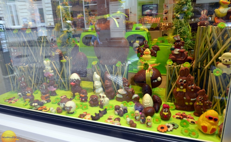 In this Easter window display, we have many chocolate eggs and chocolate bunnies, on a green background and floor.