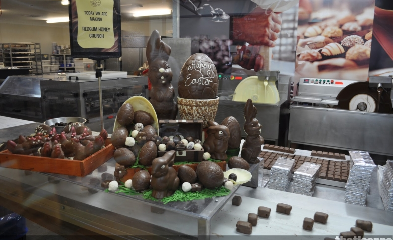 A chocolate factory with an Easter window display, designed with chocolate egg with the classic happy Easter message and a big bunny near it.