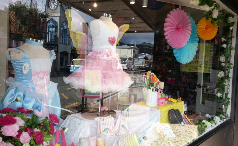 Pink fairy costumes and blue princes' costumes for kids, colorful lanterns and eggs, in this Easter window display.