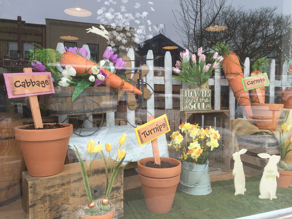 A florist way to decorate the window display, through carrots and a garden scene for Easter time.