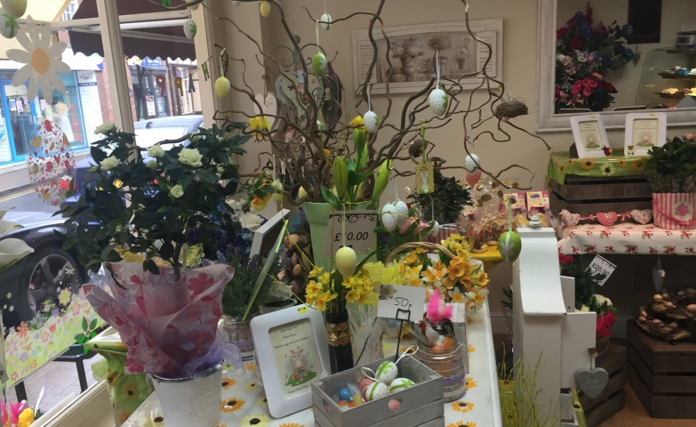 Many flowers, decorated Easter eggs, and a window display with flowers and eggs stickers.